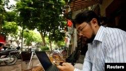 Blogger Nguyễn Chí Tuyến ở quán cafe Internet trên đường phố Hà Nội.