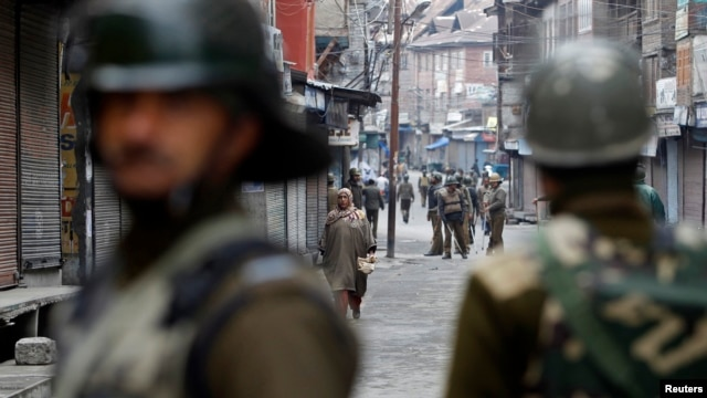 A Kashmiri woman walks as Indian police officers stand guard during a strike called by Kashmiri separatists in Srinagar, February 16, 2013.