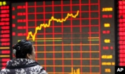 FILE - An investor looks at an electronic board showing stock information at a brokerage house in Huaibei, Anhui province, Jan. 29, 2016.