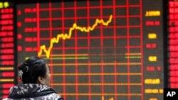 Seorang investor tengah mengamati papan elektronik yang menampilkan informasi saham di sebuah perusahaan sekuritas di Huaibei, provinsi Anhui (29/1).