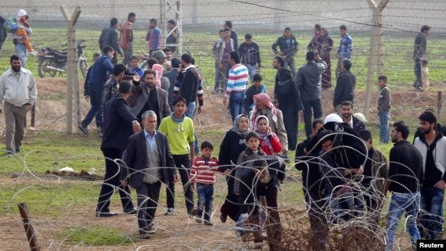 Syrians cross the border from Ras al-Ain to the Turkish border town of Ceylanpinar after an air strike by Syrian government forces, December 3, 2012.