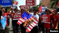 A protester holds a burning mock U.S. flag in condemnation of the strenghtened U.S. intervention under the Enhanced Defense Cooperation Agreement (EDCA) during a protest in front of the U.S. embassy in metro Manila, Philippines June 12, 2016. REUTERS/Romeo Ranoco
