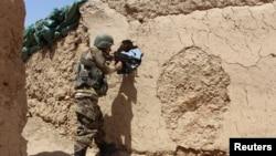 阿富汗国民军士兵在阿富汗赫尔曼德省巴巴吉一处哨所阵地严阵以待。