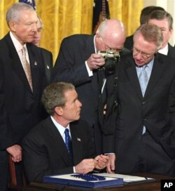 FILE - Sen Patrick Leahy, D-Vt., peers over the shoulder with his camera as President George W. Bush signs Patriot Act legislation during a ceremony in the White House East Room, Oct. 26, 2001.