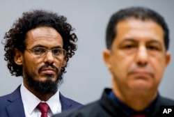 FILE - Ahmad al-Mahdi al-Faqi, left, enters the court room for his initial appearance at the International Criminal Court in The Hague, Netherlands, Sept. 30, 2015.