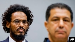 Ahmad al-Mahdi al-Faqi, left, enters the court room for his initial appearance at the International Criminal Court in The Hague, Netherlands, Sept. 30, 2015.