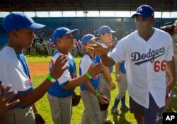 Los Angeles Dodgers player Yasiel Puig, from Cuba, greets young baseball players before giving a clinic in Havana, Cuba, Dec. 16, 2015. It was the first Major League Baseball trip to the island since 1999.