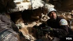 救援人员在叙利亚伊德利卜市轰炸后的废墟下寻找生还者