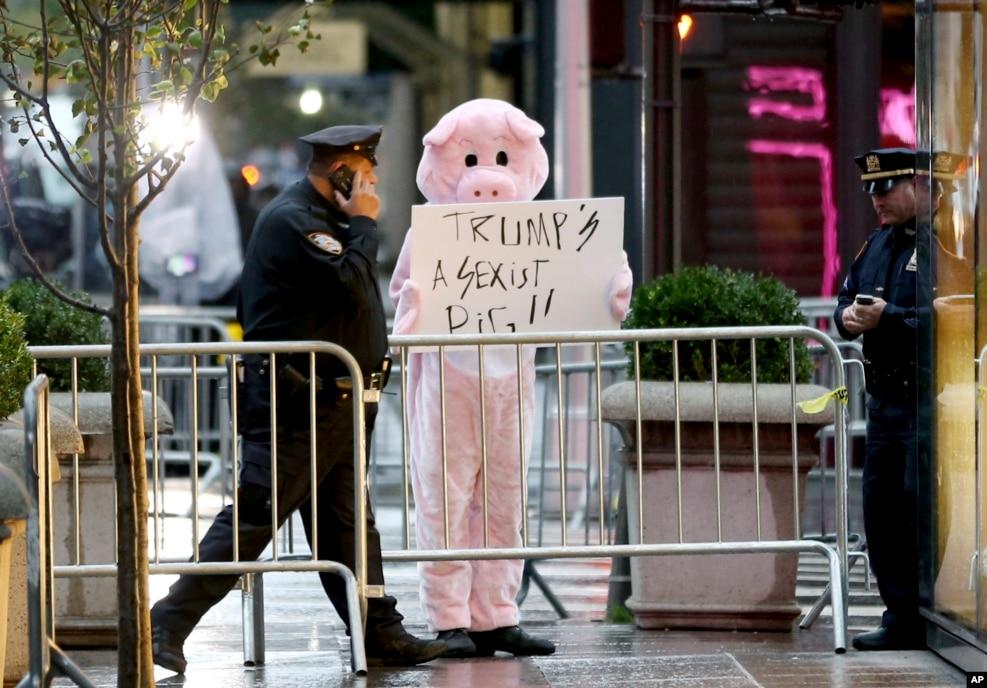 """有抗议者装扮成一头猪,在川普大楼外面展示标语""""川普是搞性别歧视的猪"""""""