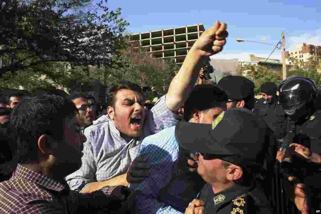 An Iranian protester chants slogans while police officers prevent him from getting near the embassy of Saudi Arabia in Tehran, Sept. 27, 2015.