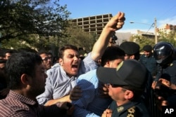 An Iranian protester chants slogans while police officers prevent him from approaching to the Saudi Arabian Embassy in Tehran, Iran, Sept. 27, 2015, during a gathering to blame the Arab country for a deadly stampede.
