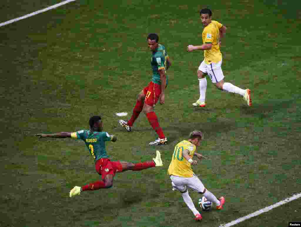 Brazil's Neymar scores past Cameroon's Nicolas Nkoulou during their match at the Brasilia National Stadium in Brasilia, June 23, 2014.