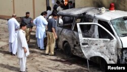 Security officials examine a damaged vehicle at the site of a suicide bomb attack in Quetta, Pakistan, August 8, 2013.