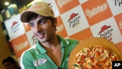 Poznati indijski glumac Zayed Khan pozira s pizzom pri otvorenju lanca Pizza Hut
