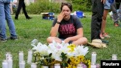 Một cư dân Charlottesville gạt nước mắt tại nơi tưởng niệm 19 người bị thương và một người thiệt mạng khi một chiếc xe tông vào những người đang rời khỏi một một cuộc biểu tình chống lại một cuộc biểu tình của những người có chủ trương thượng đẳng da trắng ở thành phố Charlottesville, bang Virginia, ngày 12 tháng 8, 2017.