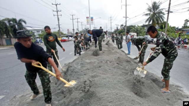 Soldiers make a bank along a street to prepare in case of more flooding in Pathum Thani province, on the outskirts of Bangkok, Thailand, October 12, 2011.