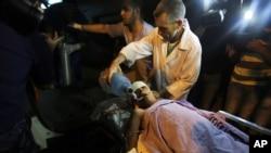 Petugas media Palestina membawa seorang anak yang terluka akibat serangan udara Israel yang menarget sebuah motor yang melintas di wilayah Beith Lahiya di Jalur Gaza (11/6).
