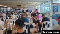 Passengers arrive and wait to be screened at Phuket International Airport (Photo by GABRIEL PIERCE)