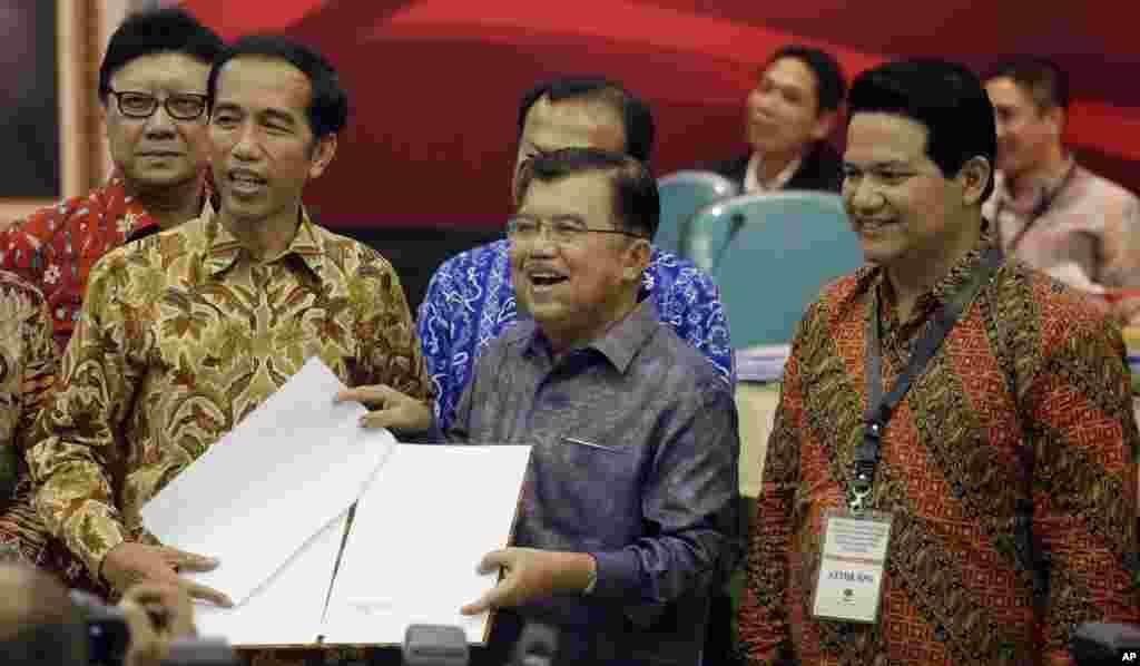 "Presiden Indonesia terpilih Joko ""Jokowi"" Widodo dan Wakil Presiden terpilih Jusuf Kalla menerima dokumen keputusan Komisi Pemilihan Umum (KPU) dari Ketua KPU Husni Kamil (kanan) di Kantor KPU (22/7). (AP/Achmad Ibrahim)"