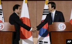 South Korean Foreign Minister Yun Byung-se, right, shakes hands with Japanese counterpart Fumio Kishida after a joint press conference in Seoul, South Korea, Dec. 28, 2015.