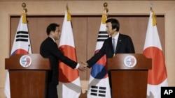 日本外相岸田文雄(左)2015年12月28日星期一在与韩国外长尹炳世会晤后在一个新闻发布会后握手。
