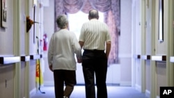 FILE - In this Nov. 6, 2015 file photo, an elderly couple walks down a hall of a nursing home in Easton, Pa.