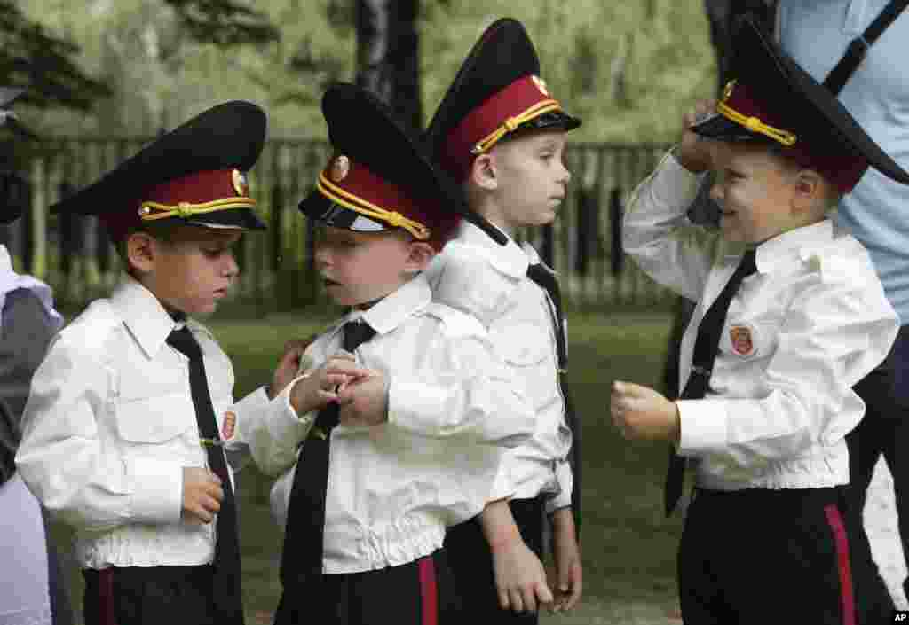 Young cadets examine their uniforms prior to a ceremony on the occasion of the first day of school at a cadet lyceum in Kyiv, Ukraine.