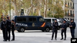 Police officers stand outside the National Court, at right, in Madrid, Spain, Nov. 2, 2017.