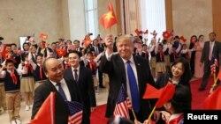 Tổng thống Donald Trump trao lá cờ Mỹ cho Thủ tướng Nguyễn Xuân Phúc và bản thân ông cầm lá cờ Việt Nam để vẫy chào đám đông trong chuyến công du đến Hà Nội vào ngày 27/2/2019.