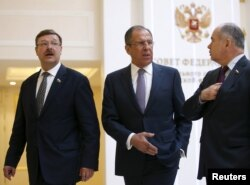 Russian Foreign Minister Sergei Lavrov, center, Konstantin Kosachyov, left, Chairman of the Federation Council Committee on Foreign Affairs, and Ilyas Umakhanov, Deputy Chairman of the Federation Council, leave a session of the Federation Council in Moscow, May 20, 2015.