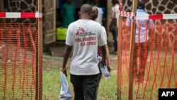 Des membres de l'équipe de Médecins Sans Frontières (MSF) traversent une zone de sécurité Ebola à l'entrée de l'hôpital de référence Wangata à Mbandaka, au nord-ouest de la RDC, le 20 mai 2018.