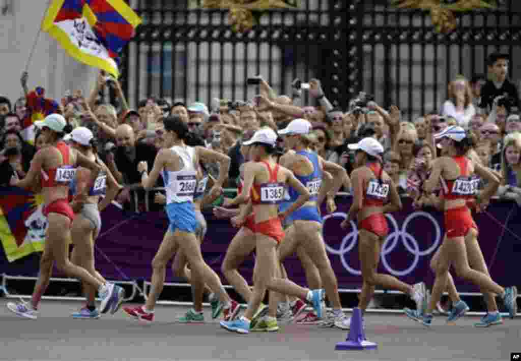 A Tibetan flag, left, pass Buckingham Palace at the 2012 Summer Olympics, Saturday, Aug. 11, 2012, in London.