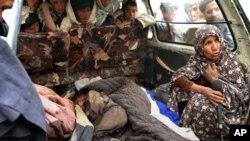 아프가니스탄 남부 칸다하르주에서 11일 발생한 미군의 총격사건으로 사망한 손자의 시신을 지키는 한 여성