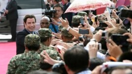 American actor John Travolta (L) shakes hands with fans as he arrives for the launch ceremony of the Qingdao Oriental Movie Metropolis on the outskirts of Qingdao, China, September 22, 2013.