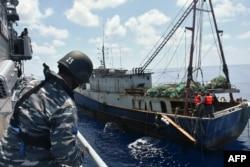 KRI Imam Bonjol-363 (kiri) menahan kapal nelayan China di perairan Natuna, 21 Juni 2016. (Foto: TNI AL via AFP)