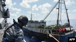 KRI Imam Bonjol-363 (kiri) menahan kapal nelayan China di perairan Natuna pada 21 Juni 2016. (Foto: TNI AL via AFP)
