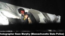 Tsarnaev sale del botedonde se escondía, con la cara pintada por las mirillas láser de las armas de la policía.