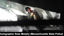 FILE - An injured Dzhokhar Tsarnaev is seen emerging from the boat in which he was hiding from police.