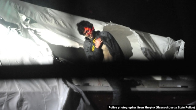 An injured Dzhokhar Tsarnaev emerges from the boat where he'd been hiding during the police manhunt for him, in Watertown, Massachusetts, April 19, 2013.
