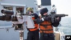 Dua tentara Norwegia menggunakan riffle dan senapan mesin kaliber 0,50 dalam latihan tempur rutin di kapal pendukung Norwegia Valkyrien, di Laut Baltik, sepanjang Pantai Jerman, Jerman, 22 April 2014. (Foto: dok).