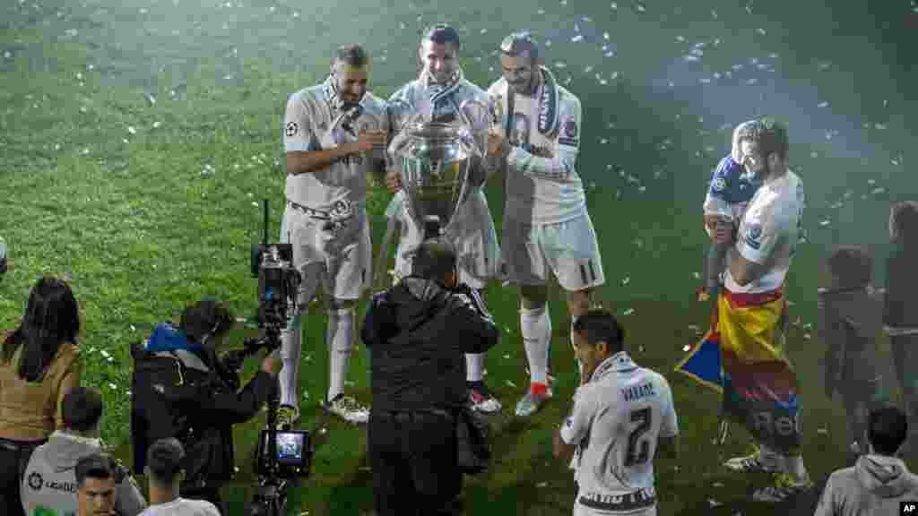 Les joueurs du Real Madrid Karim Benzema, Cristiano Ronaldo et Gareth Bale posent pour une photo avec le trophée qu'ils ont remporté, le 29 mai 2016.