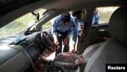 Pakistan polisi suikaste uğrayan Butto davası savcısı Zülfikar Chaudry'nin arabasından kanıt topluyor.