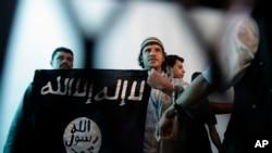 Umurwanyi wa Al Qaida muri Yemeni afise ibendera ry'uwo muhari mugihe yari imbere ya sentare i Sanaa, Yemen.