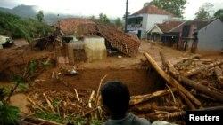 Seorang warga desa berdiri di dekat sebuah rumah yang hancur akibat longsor yang melanda desa Pasir Panjang, Brebes, 23 Februari 2018. (Foto: Antara/OKy Lukmansyah/via REUTERS).
