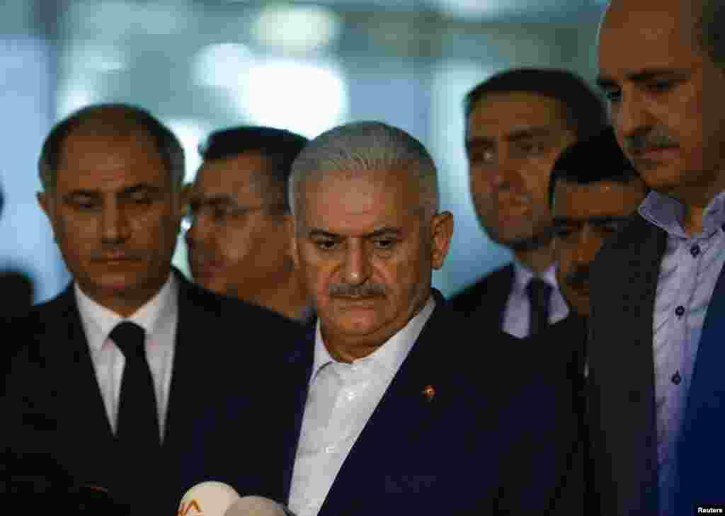 Perdana Menteri Turki Binali Yildirim (tengah) berbicara kepada wartawan didampingi Menteri Dalam Negeri Efkan Ala (kiri) di bandar udara Ataturk di Istanbul, Turki, menyusul sejumlah ledakan bom bunuh diri (29/6). (Reuters/Murad Sezer)