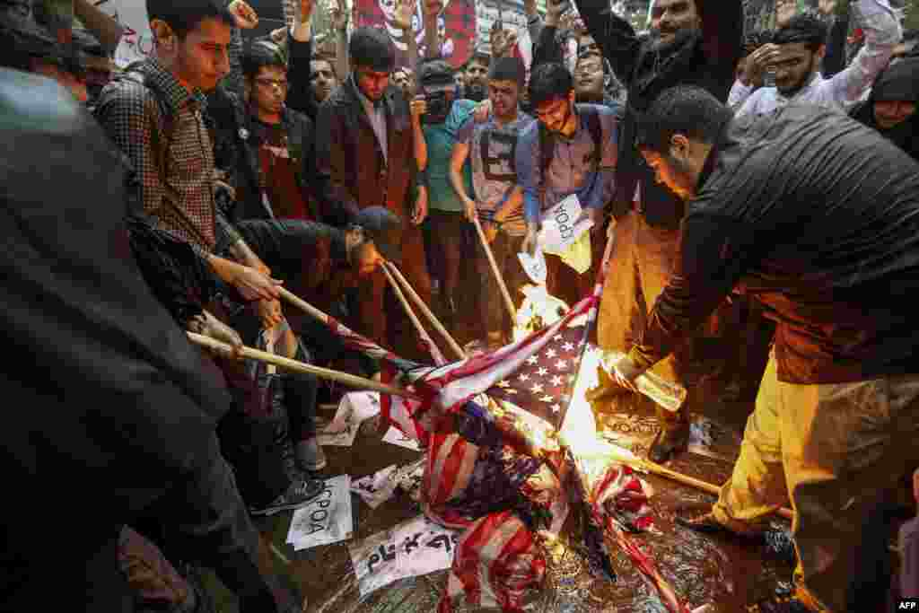 Iranians burn U.S. flags during a demonstration outside the former U.S. embassy headquarters in the capital Tehran. Iranians reacted with a mix of sadness, resignation and defiance to U.S. President Donald Trump's withdrawal from the nuclear deal, with sharp divisions among officials on how best to respond.