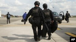 Members of the US Secret Service's Counter Assault Team, known in the agency as CAT, walk across the tarmac at Kortrijk-Wevelgem International Airport, March 26, 2014, in Waregem, Belgium.