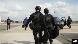 美国特勤局反攻击组成员走在比利时瓦雷赫姆的科特里克-韦弗尔海姆国际机场的跑道上。(2014年3月26日)