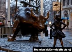 """纽约华尔街附近著名的铜牛像对面,树立起""""无畏女孩""""铜像,迎接国际妇女节(2017年3月7日)"""