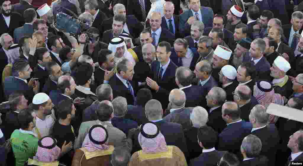 Syria's President Bashar al-Assad speaks with people after attending Eid al-Fitr prayers at Anas bin Malek mosque in Damascus, August 8, 2013. (SANA)
